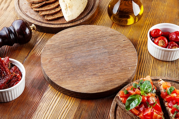 Top view empty cutting board for pizza or meat. blank board for serving food in composition with, sun-dried tomatoes, bruschetta and utensils on wooden background. flat lay