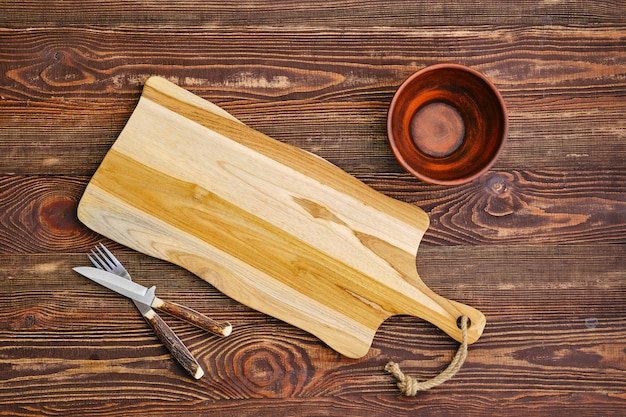 Top view of empty cutting wooden board with clay bowl and fork with knife on the table