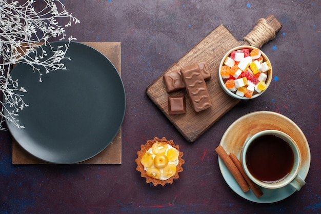 Top view of empty dark plate round formed with tea and candies on the dark surface