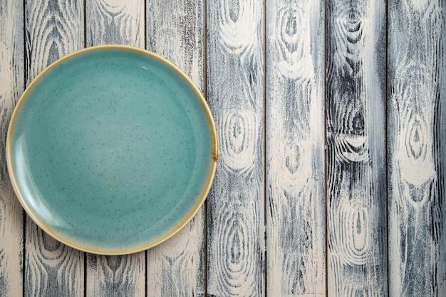 Вид сверху пустая стеклянная тарелка зеленого цвета на серо-деревенской поверхности