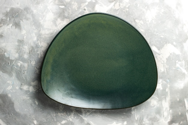 Top view empty green plate isolated on light-grey desk.