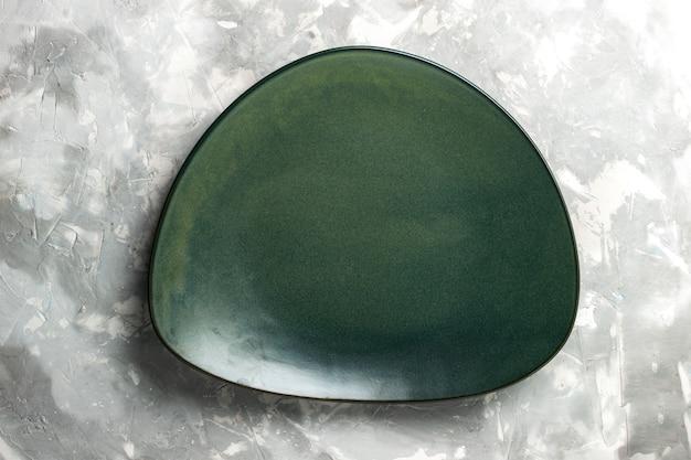 Вид сверху пустая зеленая тарелка, изолированных на светло-сером столе.