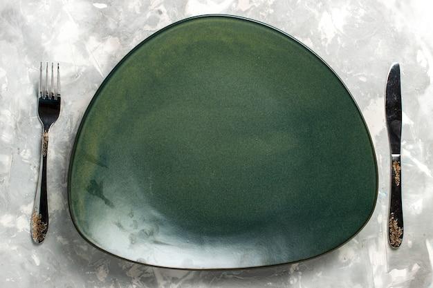 Vista dall'alto piatto verde vuoto isolato con forchetta e coltello sulla scrivania grigio chiaro.
