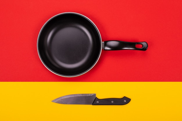 Top view of empty kitchen frying pan with kitchen knife on red-yellow