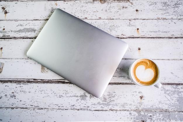 Вверх посмотреть пустой ноутбук и чашку кофе на столе