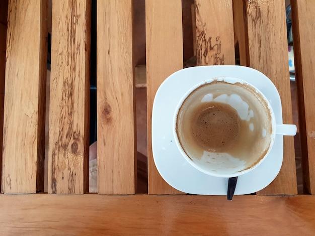 木製のテーブルの上のビュー空のラテコーヒーカップ
