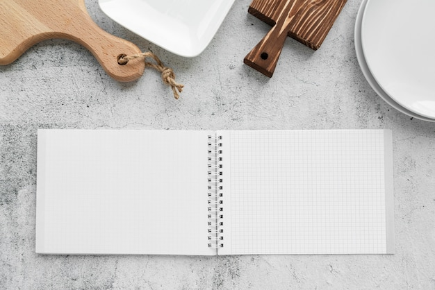 Top view of empty menu notebook with chopping boards and plates