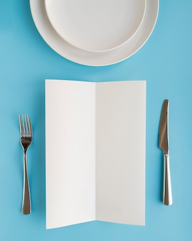 Top view of empty menu paper with plates and cutlery