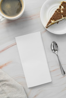 Top view of empty menu paper with spoon and plate of cake