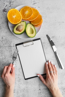 Top view of empty menu with avocado and orange slices