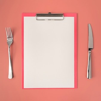 Top view of empty menu with cutlery
