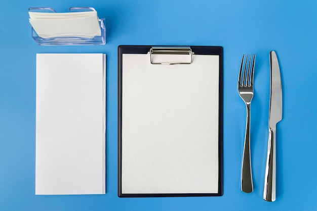 Top view of empty menu with fork and knife