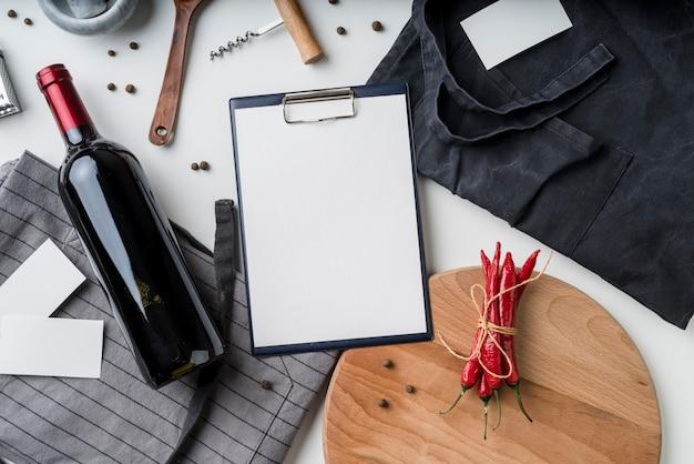 Vista dall'alto del menu vuoto con bottiglia di vino e peperoncino