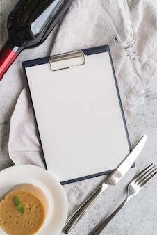 Top view of empty menu with wine bottle and cutlery