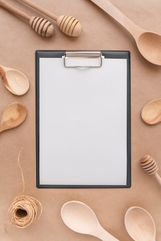 Top view of empty menu with wooden spoons and honey dippers