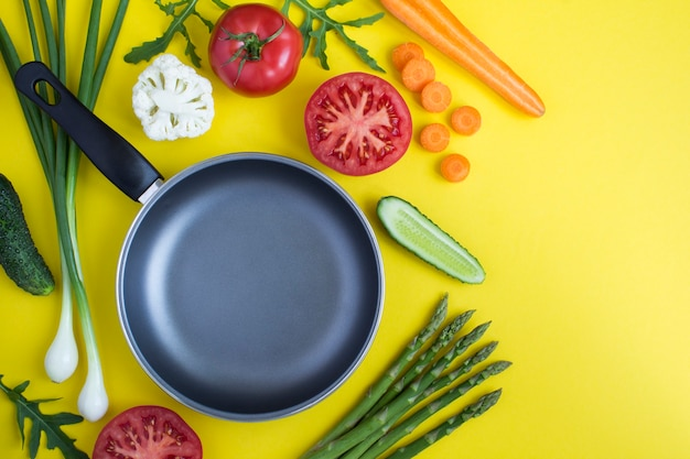 Top view of empty metal frying pan and vegetables on the yellow  background. copy space. close-up.