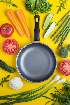 Top view of empty metal frying pan and vegetables on the yellow  background. location vertical.