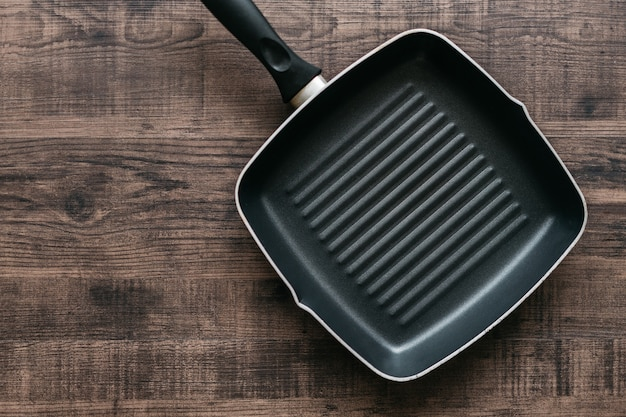Top view of the empty non-stick square frying pan over wooden kitchen counter background with copy space.
