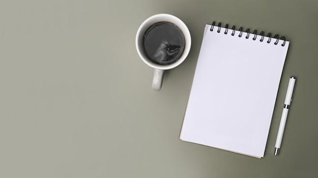Вид сверху пустой блокнот, ручка и чашка кофе на сером фоне.