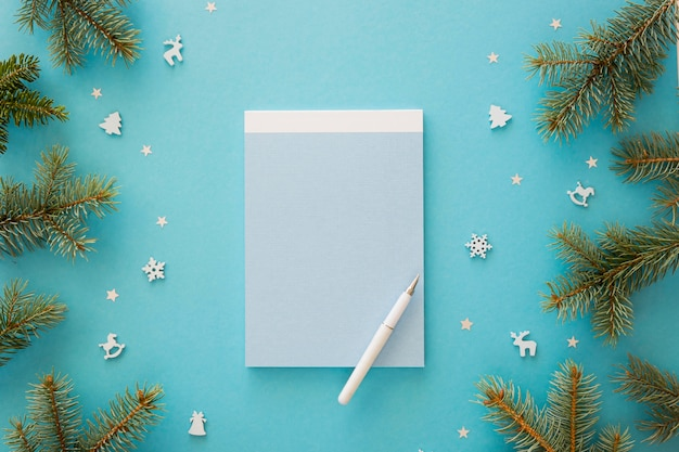 Top view empty notepad surrounded by christmas elements