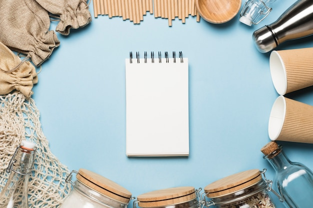 Top view empty notepad with eco friendly objects