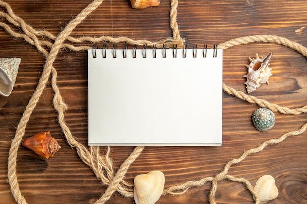 Blocco note vuoto vista dall'alto con corde e conchiglie sulla scrivania marrone