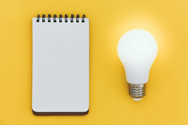 Top view of empty open lined notebook and led light bulb on yellow background ideas concept