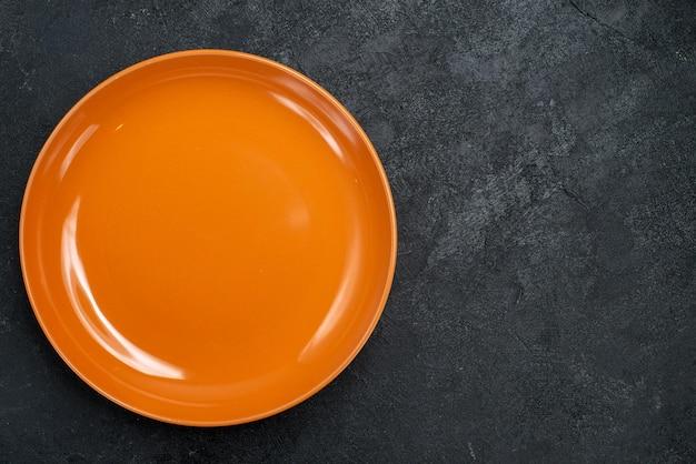 Vista dall'alto di vetro arancione vuoto realizzato sulla superficie scura