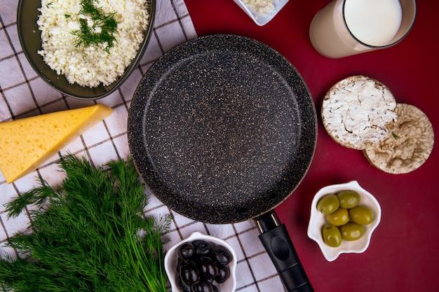 Vista dall'alto di una padella vuota e un pezzo di formaggio con olive in salamoia e torte di riso su tessuto plaid su rosso