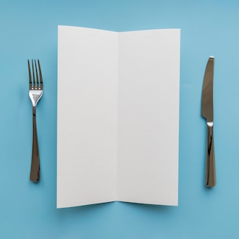Top view of empty paper with fork and knife