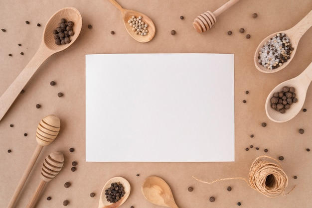 Top view of empty paper with wooden spoons and condiments