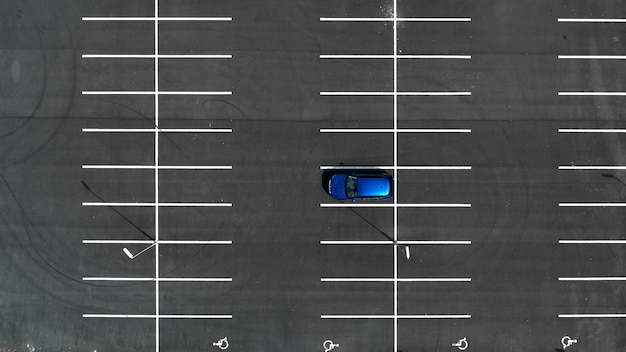 Top view on empty parking lots with one blue car