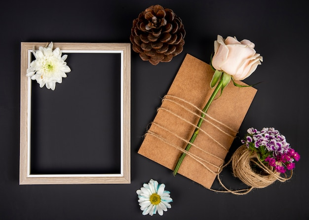 Top view of an empty picture frame and brown paper greeting card with white color rose tied with a rope and turkish carnation with daisy flowers and cone on black table
