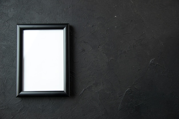 Top view of empty picture frame on the dark wall