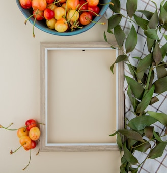 Top view of an empty picture frame and fresh ripe rainier cherries in a bowl with green leaves on white