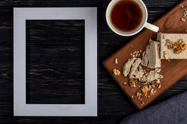 Top view of an empty picture frame and halva with sunflower seeds and walnuts on a wooden board and a cup of tea on rustic