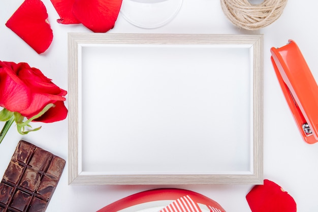 Top view of an empty picture frame with a ball of rope red color rose and dark chocolate and stapler on white background with copy space