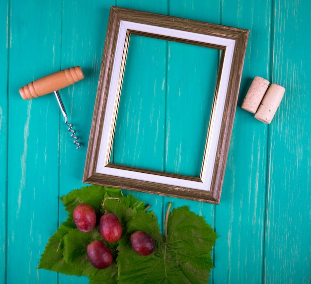 Top view of an empty picture frame with bottle screw , wine corks and sweet grapes with green grape leaves on blue wooden table