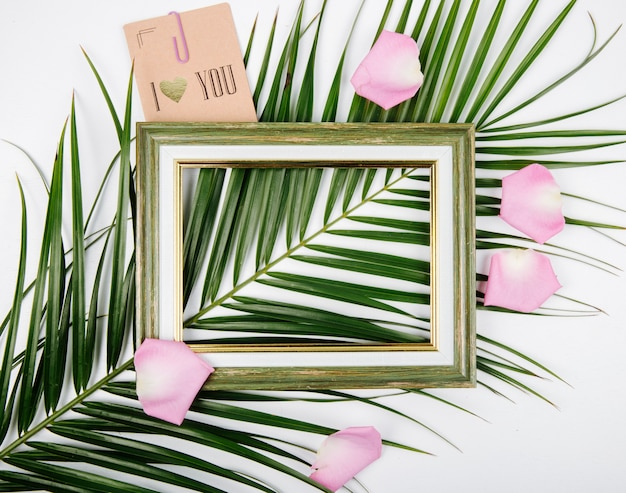 Top view of an empty picture frame with postcard on a palm leaf with rose flower petals on white background