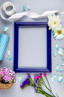 Top view of an empty picture frame with purple and pink color statice flowers and chrysanthemum flowers and petals, a ball of rope with turkish carnation on white table with copy space