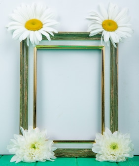Top view of an empty picture frame with white color chrysanthemum and daisy flowers on white background with copy space