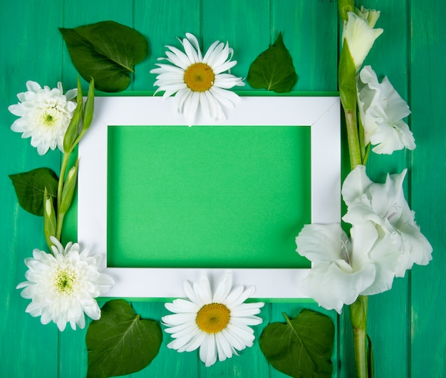 Top view of an empty picture frame with white color chrysanthemum gladiolus and daisy flowers on green color background with copy space