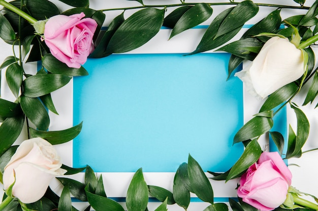 Top view of an empty picture frame with white and pink roses and ruscus on blue background with copy space