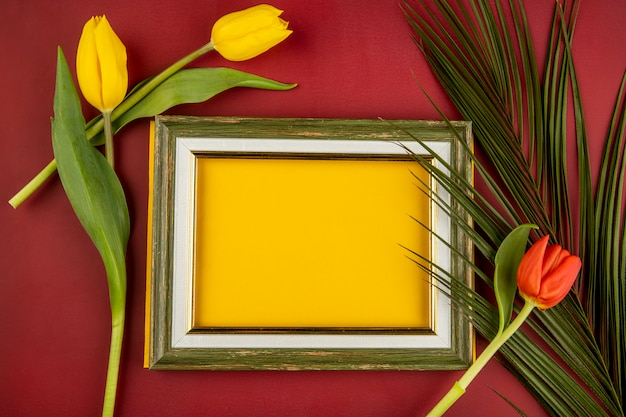 Top view of an empty picture frame and yellow and red color tulips with palm leaf on red table