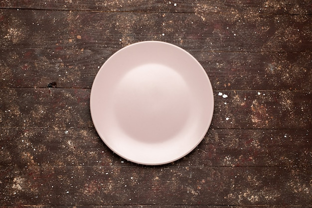 Top view of empty pink plate isolated on brown rustic, wood plate wooden