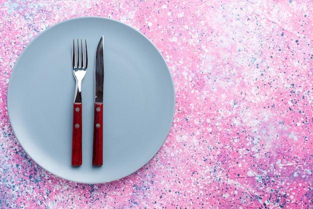 Вид сверху пустая тарелка синего цвета с вилкой и ножом на розовом столе цветная фото тарелка столовые приборы для еды