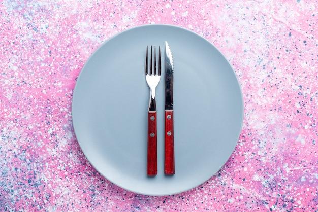 Vista dall'alto piatto vuoto di colore blu con forchetta e coltello su posate per alimenti con piastra fotografica a colori rosa brillante