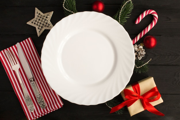 Top view of empty plate and christmas composition on the black