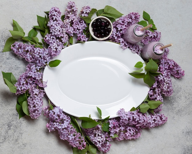 Top view empty plate over hyacinth flowers with smoothie