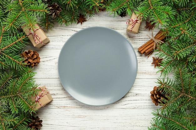 평면도. 빈 접시 라운드 나무 테이블에 세라믹입니다. 크리스마스 장식으로 휴일 저녁 식사 접시 개념